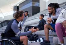Wheelchair Athlete Showing Smart Phone To Friend In Stadium Bleachers