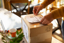 Business Owner Placing Shipping Label On Cardboard Box