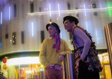 Fashionable Couple Below Neon City Building At Night