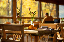 Wildflower Bouquet And Autumn Gourds On Rustic Cafe Table