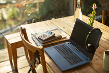 Laptop, Headphones, Calculator And Notebooks On Cafe Table