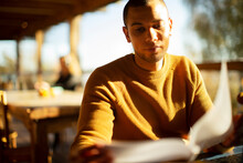 Businessman Reviewing Paperwork In Sunny Cafe