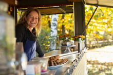 Portrait Happy Female Food Cart Owner Working In Park