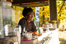 Happy Female Food Cart Owner In Sunny Park
