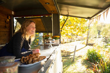 Happy Female Food Cart Owner In Sunny Autumn Park