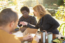 Businesswomen Discussing Paperwork And Eating Lunch At Table In Park