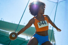 Female Track And Field Athlete Throwing Discus Under Sunny Blue Sky