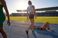 Tired Female Track And Field Athlete Laying On Track After Competition
