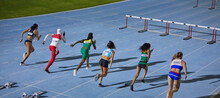 Female Track And Field Athletes Racing Toward Hurdles In Competition