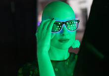 Portrait Stylish Woman With Shaved Head In Neon Glasses In Green Light