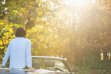 Young Man In Convertible Relaxing Enjoying Sunny Autumn Park Trees