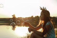 Girl Blowing Bubbles By Lake