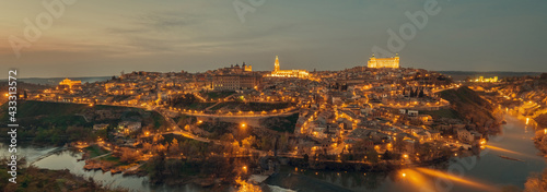 Fotografía Aerial drone point of view illuminated with night street lights Toledo historical picturesque city of Spain surrounded by Tagus river located on hilltop, evening scene view