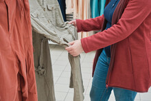 Caucasian Pregnant Woman In Store Chooses To Buy A Spacious Dress Of Light Green Color. Concept Of Buying New Clothes, Fashion, Beauty And An Active Lifestyle While Carrying Child. Hands Close Up Shot