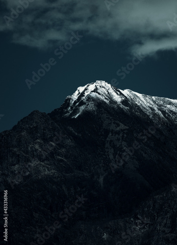 Vertical shot of a rocky mountain covered with snow under a cloudy sky Tapéta, Fotótapéta