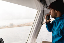 Young Skipper Man Sailing A Boat Working During Summer Vacation - Focus On Face