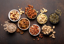 Selection Of Assorted Raw Nuts And Various Seeds In Bowls On Brown Stone Background From Above, Healthy Source Of Energy, Fat And Vegetarian Protein
