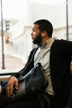 Young Man Traveling On Light Train Wearing Earphones