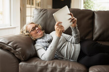 Senior Woman Reclining On Sofa Looking At Digital Tablet
