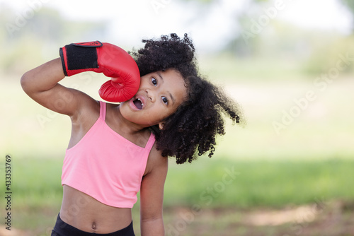 African children curly hair wearing boxing red glove and punching her face. - fototapety na wymiar