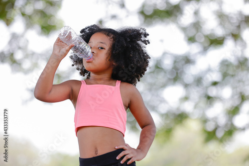 Little girl drinking water from plastic bottles after exercise at outdoor - fototapety na wymiar