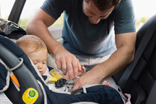 Mid Adult Man Fastening Safety Belt On Baby Daughters Car Seat