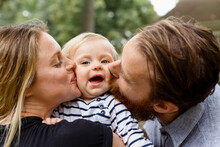 Mother And Father Kissing Baby Girl On Cheek, Outdoors