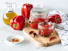 Close Up Of Jars Of Roasted Red Peppers Surrounded By Ripe Red Peppers, Dried Peppers And Chili Flakes.