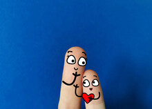 Two  Fingers Are Decorated As A Parent And A Child. They Are Happy.