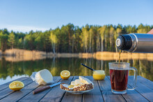 Pouring Hot Tea Into A Glass Mug From A Thermos In The Morning Next To The Lake And Forest. Breakfast On A Wooden Table