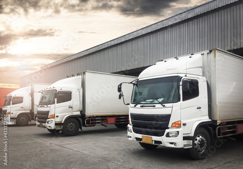 Container Trucks Parked Loading at Dock Warehouse. Shipping Warehouse Logistics.Cargo Shipment.  Industry Freight Truck Transportation.   - fototapety na wymiar