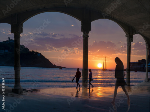 Canvas-taulu Una joven y una pareja pasean por la playa de La Concha, en San Sebastián, España