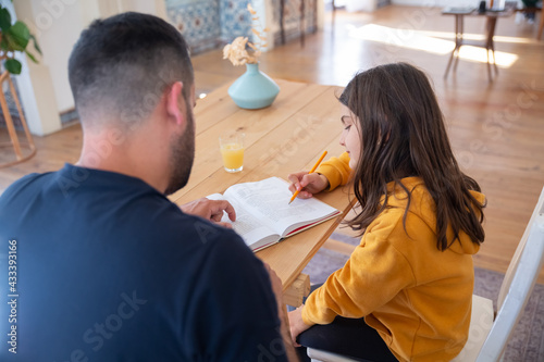 Fototapeta Back view of father and daughter reading book together. Cheerful brunette girl doing task, sitting at table with bearded dad. Home education, family time concept obraz