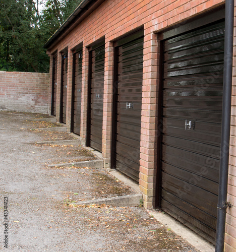 Obraz na plátně A block of modern non-descript garages with freshly painted black metal doors