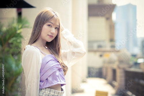 Fotografia Asian beautiful female with bronze long hair in purple camisole and white sleeve stands on the street as background on a sunny morning