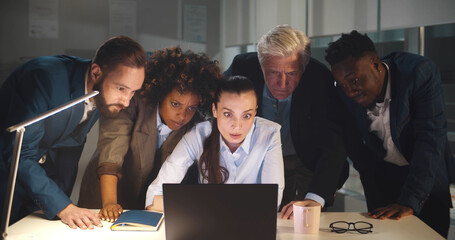 Diverse group of business people in office at night looking at laptop screen