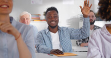 Smiling African Student Sitting At Desk And Raising Hand In Classroom