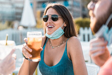 Woman Holding An Iced Tea Glass With Lowered Face Mask In Coronavirus New Normal Time.