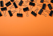 Black Binder Clips On Orange Background, Flat Lay. Space For Text
