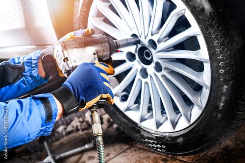 Man mechanic with car tire in service center. - fototapety na wymiar