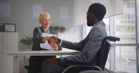 African disabled job candidate and mature female employer shaking hands and smiling at camera