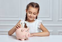 Little Child Girl With Piggy Bank At Home