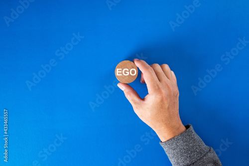 Fototapeta Hand holding a round wooden block  with the word ego written on it