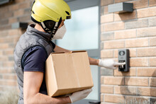 Courier In Green Helmet Wearing Mask And Gloves Holds A Parcel Box And Staying Near Front Door Of House. Ring The Door Bell And Waiting For Customer To Come Out.