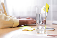 Selective Focus Of Glass With Water Near Man Typing On Laptop On Blurred Background, Cropped View