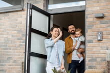 Young Parents With Newborn Kid Customer Order Food Delivery Online And Standing In Front Of The House To Receive It. Housewife Waving Goodbye To Courier And Father Holding A Son.
