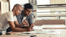 Two Black Man Coworkers Carpenters  Examining Blueprint  And Checking A List Of Daily Assignment.Preparing For Job.