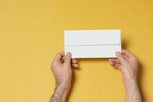 Hands Holding A Letterhead Paper Envelope On Yellow Background