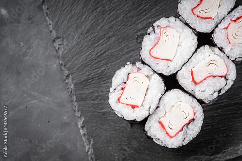 Fotografia appetizing sushi roll maki with crab stick on a black stone plate