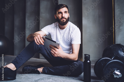 Athletic male sitting with tablet on floor in gym Fotobehang
